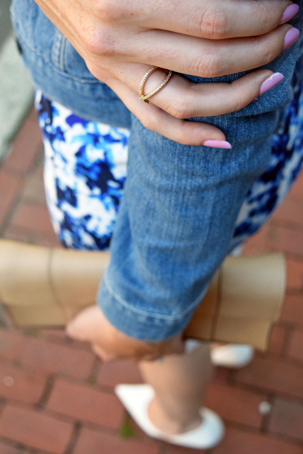 pink nails and gold criss-cross ring