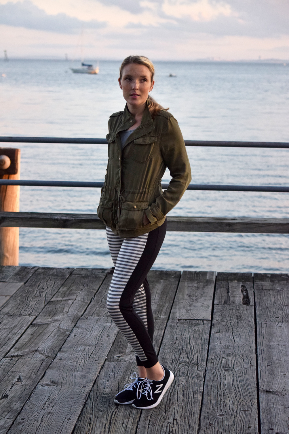 green military jacket with striped joggers and sneakers