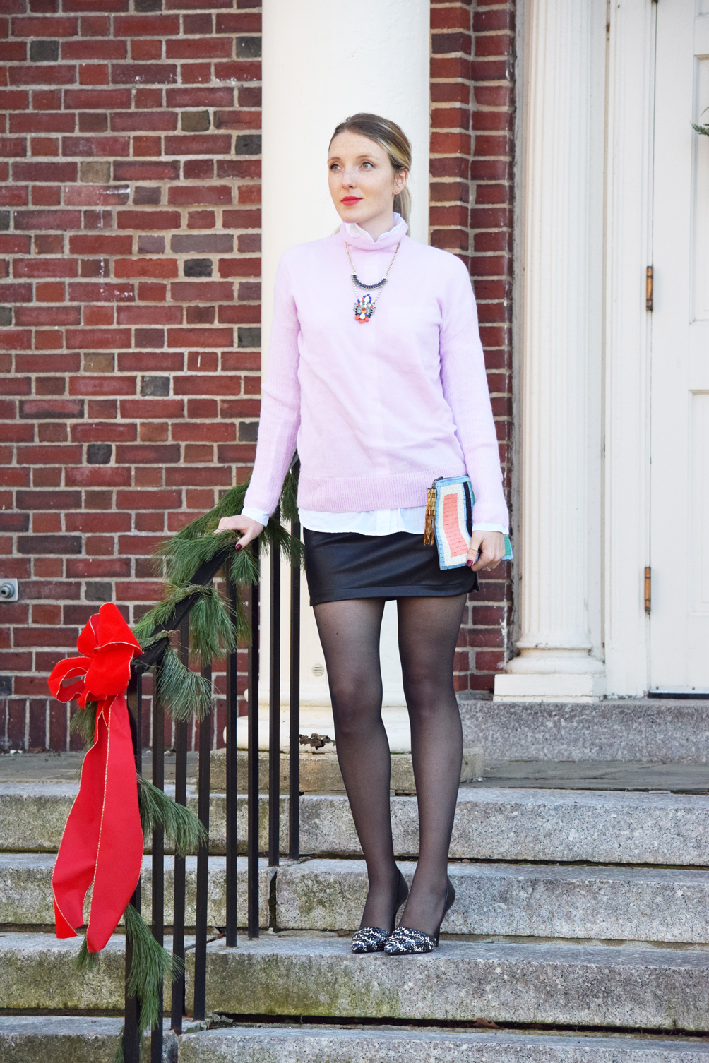 pastel turtleneck sweater with a faux leather mini skirt