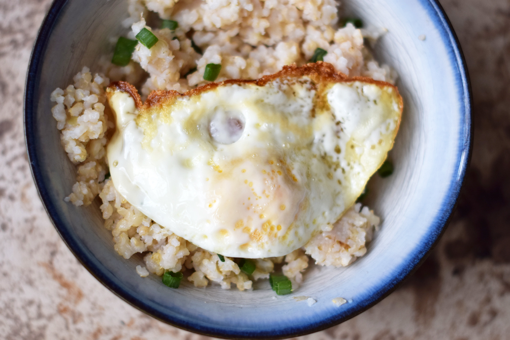 brown rice bowl with a fried egg and avocado - one brass fox