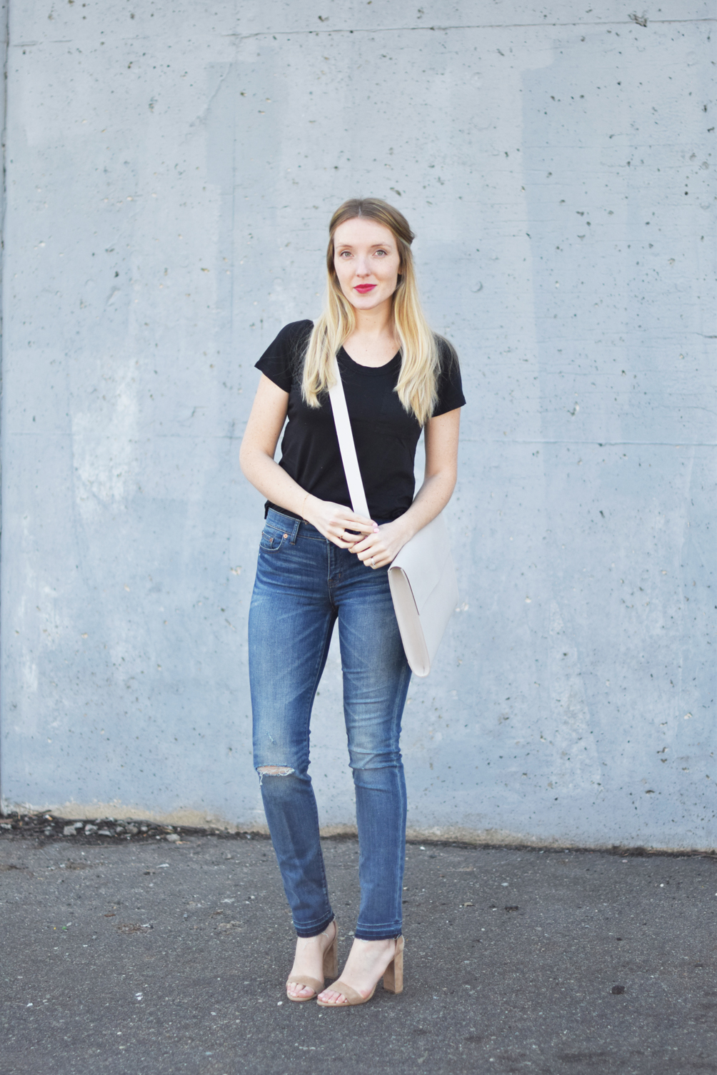 women's minimal outfit with distressed denim, a basic tee, block heels, and portfolio bag - one brass fox