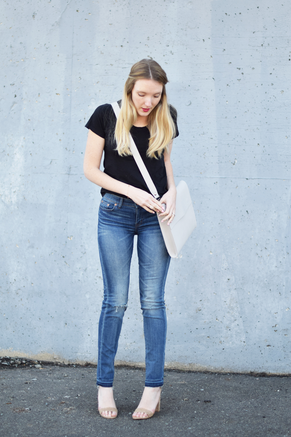 women's spring outfit with a basic tee, distressed denim, block heel sandals, and portfolio bag - one brass fox
