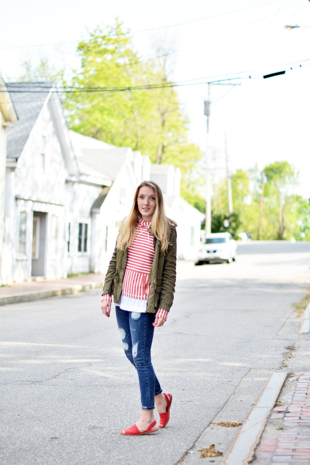 spring style, nautical striped hoodie with destructed denim, red slide sandals, and an army green jacket, leslie musser of one brass fox