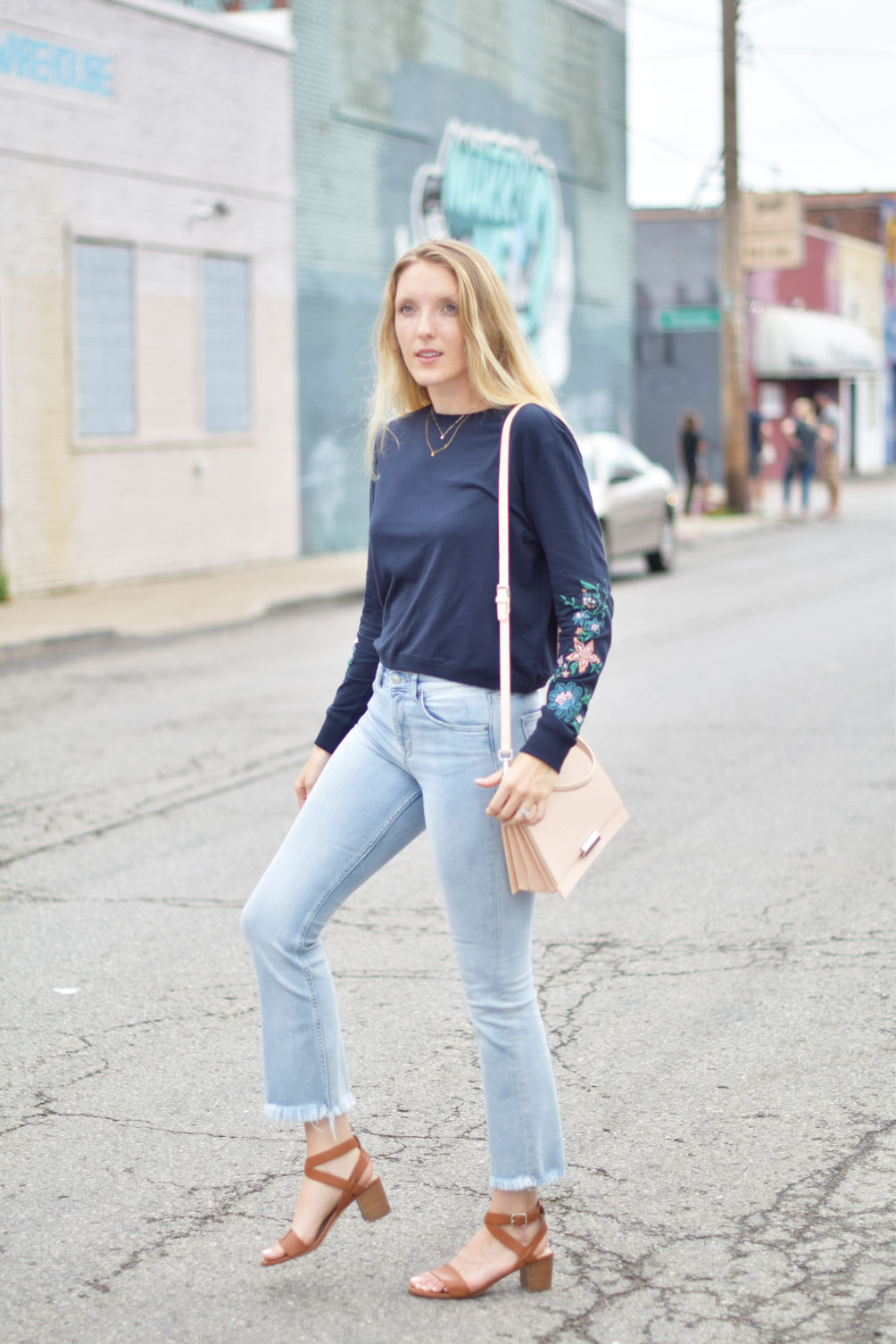 Leslie Musser wears kick flare denim with an embroidered sweatshirt and structured blush purse on one brass fox
