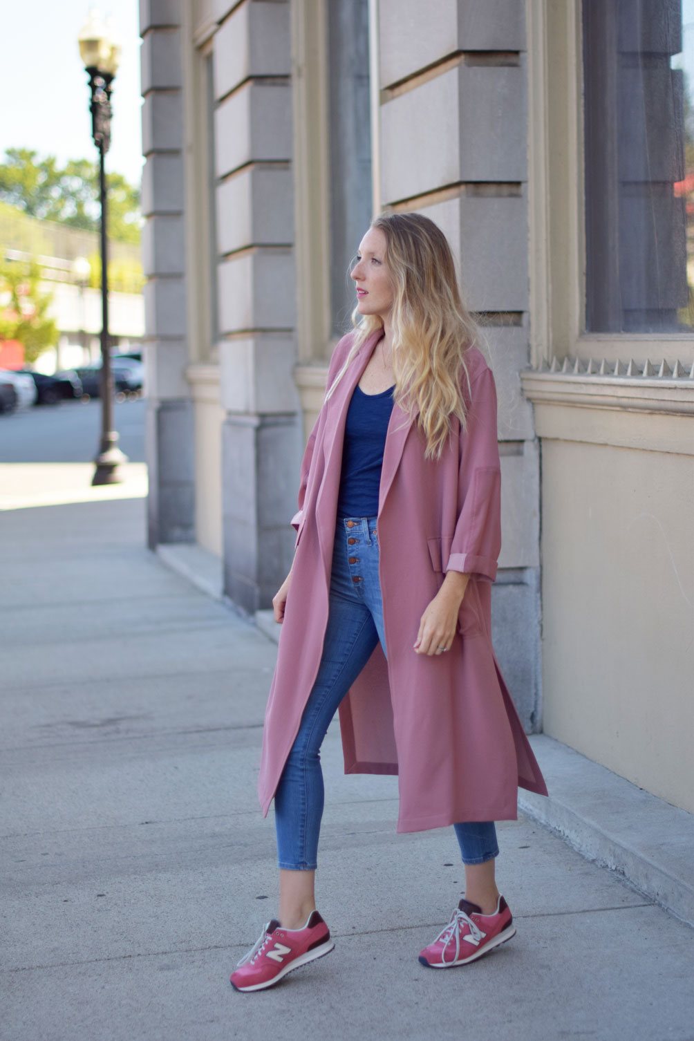 Leslie Musser wears a paneled duster coat with button-fly jeans and pink sneakers on one brass fox