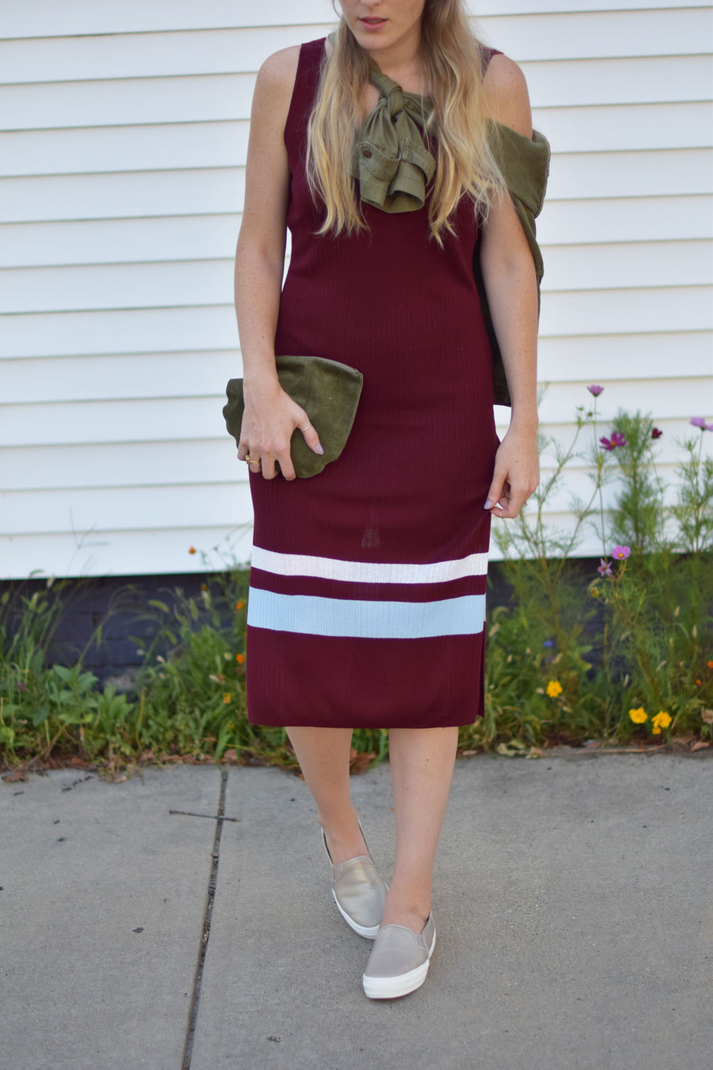 the perfect early fall outfit in a ribbed knit dress with slip-on platform sneakers and an army green jacket on Leslie Musser of one brass fox