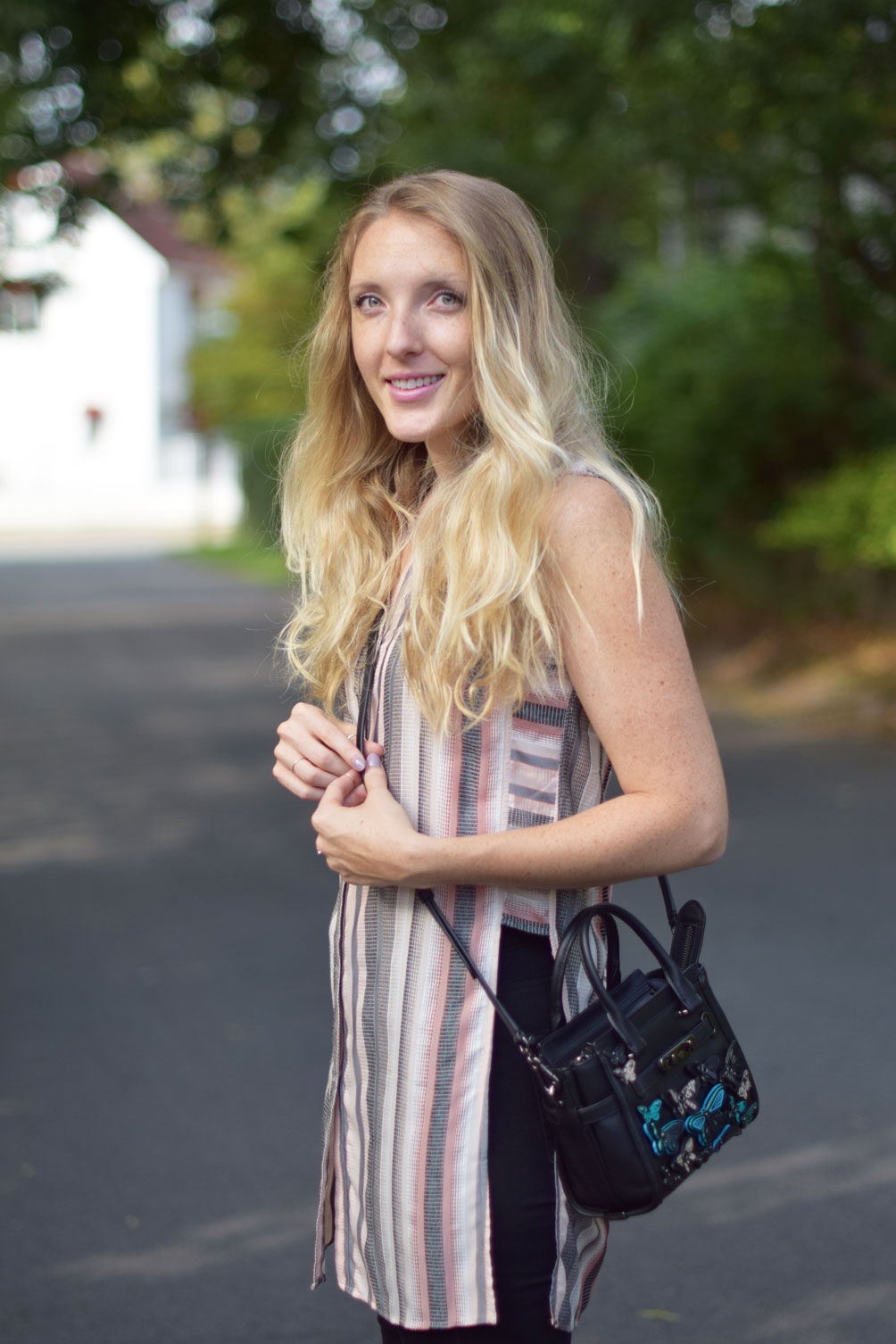 Leslie Musser wears a sleeveless tunic top with black skinny jeans and a butterfly embellished Coach bag on one brass fox