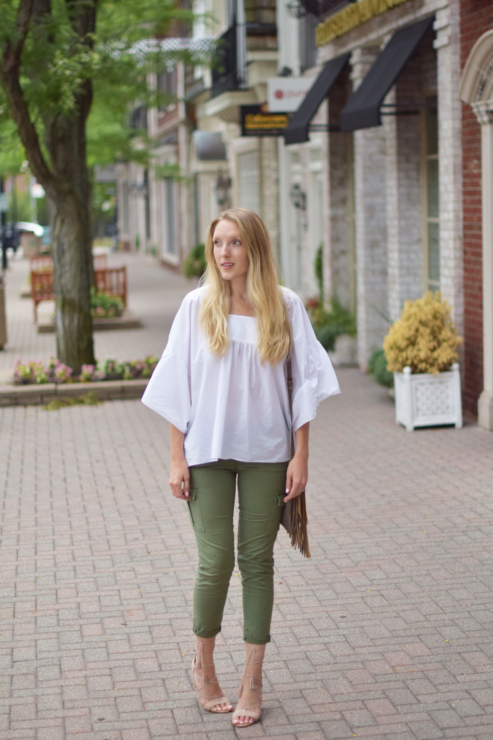 Leslie Musser wears utility cargo pants with lace up sandals and a fringe crossbody bag on one brass fox