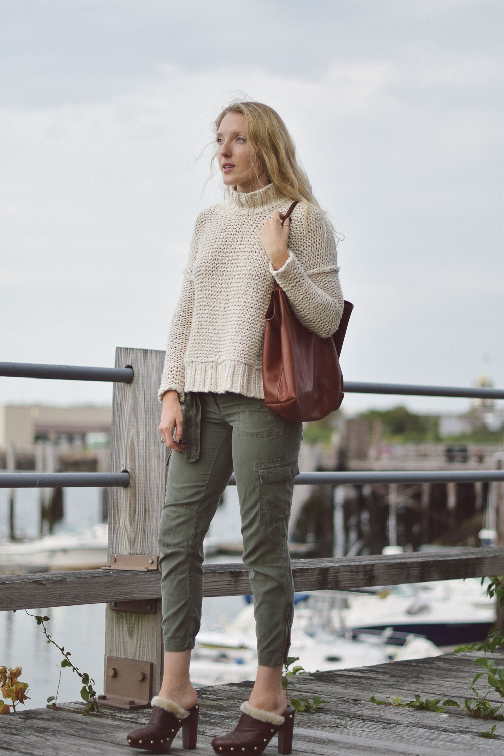 Free People chunky knit sweater with AG cargo pants and faux fur clogs on Leslie Musser one brass fox