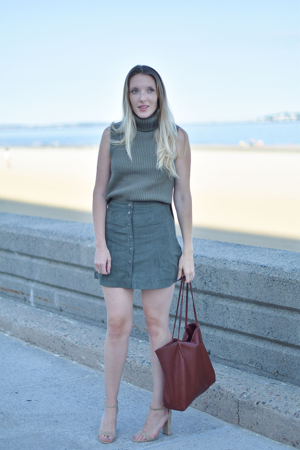 styling a suede skirt for fall with a cozy knit vest and leather tote bag on Leslie Musser of one brass fox