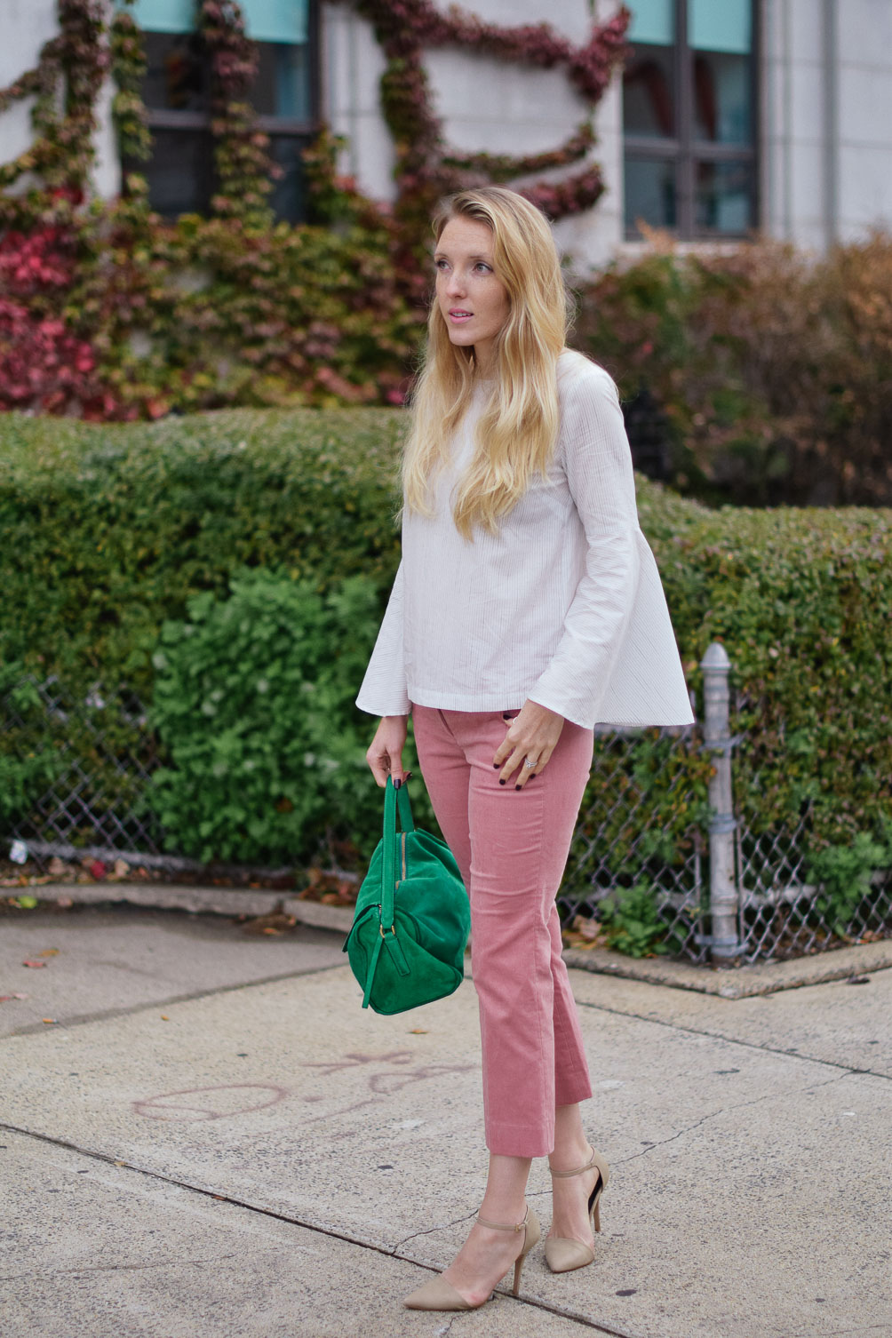 Leslie Musser wears cropped blush corduroys with a striped bell sleeve top and emerald tote on one brass fox