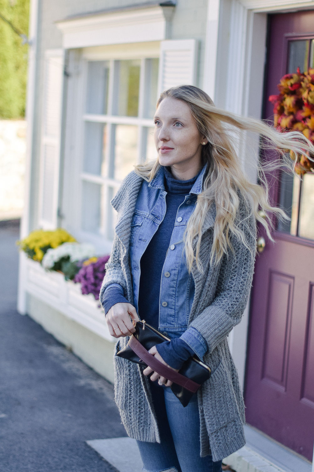 Leslie Musser styling an open knit cardigan with denim jacket and distressed jeans for fall style on one brass fox