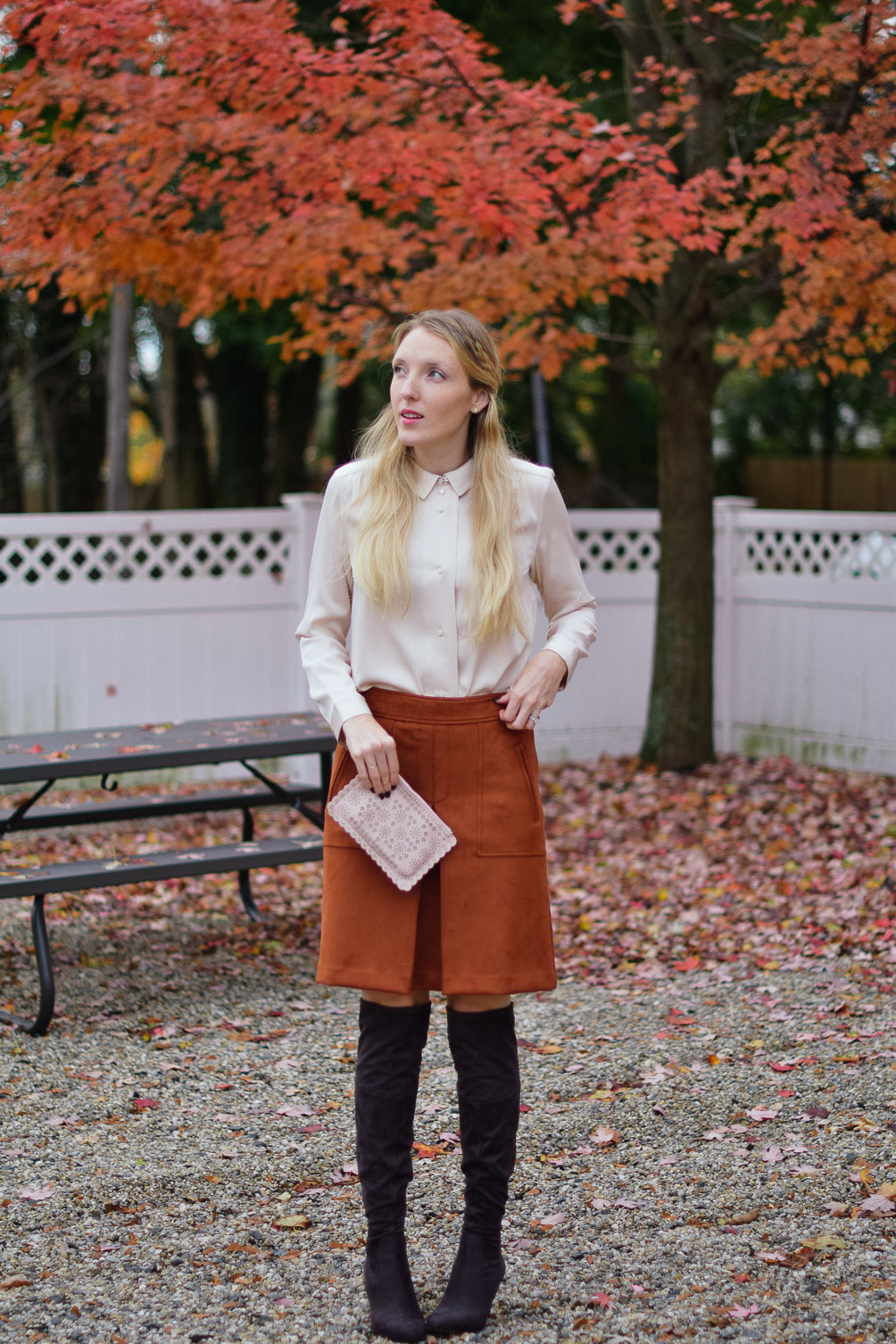 Leslie Musser wearing a rust suede skirt with blush blouse and over the knee boots on one brass fox