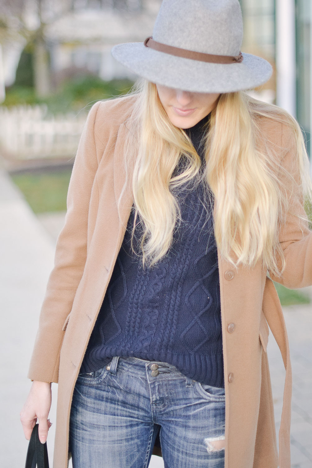 styling a grey felt fedora with camel winter coat and cable knit sweater