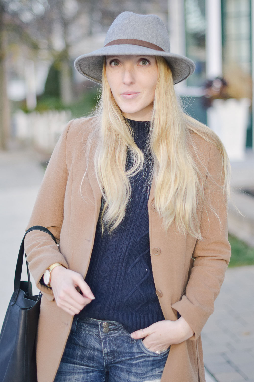 styling a grey felt fedora with winter camel coat and cable knit sweater