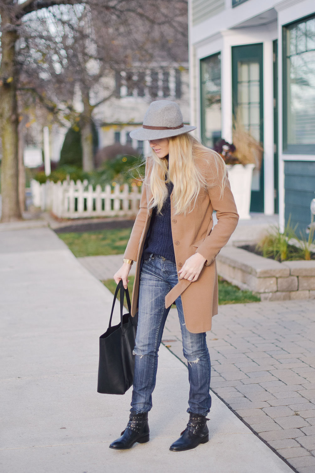 styling a camel winter coat with distressed jeans and cable knit sweater