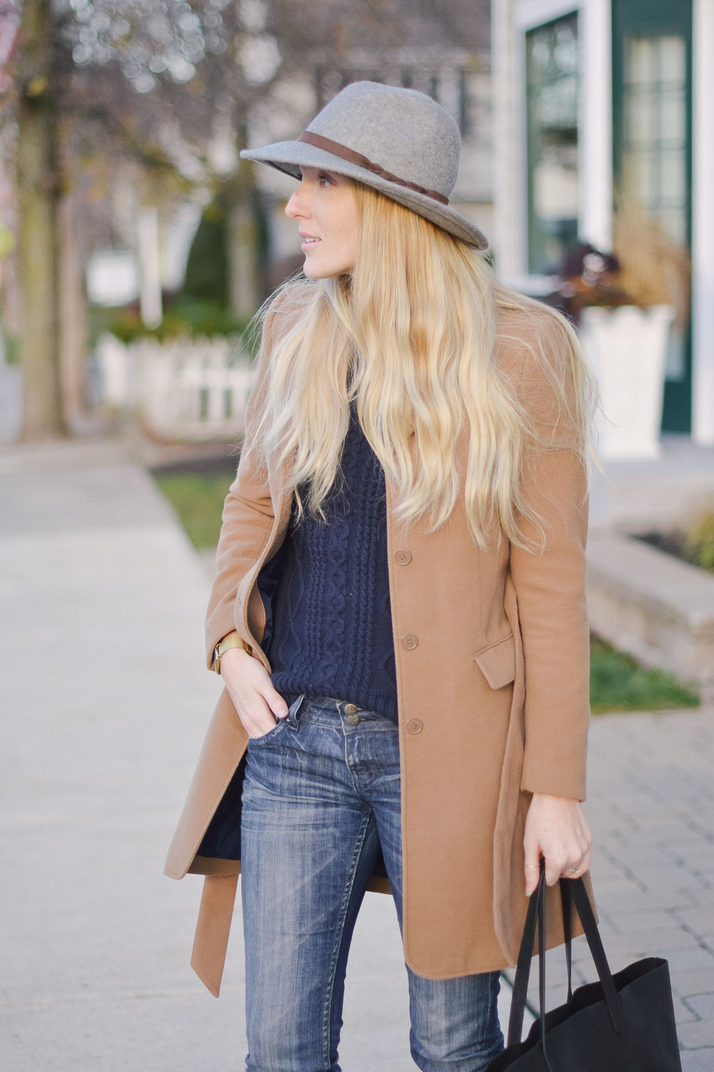 styling a camel winter coat with felt fedora, cable knit sweater, distressed boyfriend jeans and buckle boots