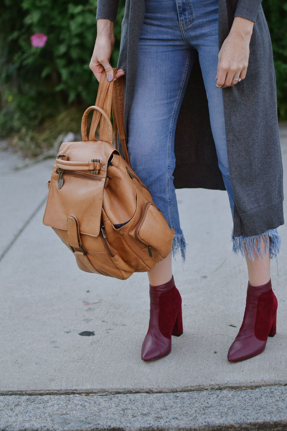 Leslie Musser wearing fringe hem jeans with a duster sweater and suede oxblood boots on one brass fox