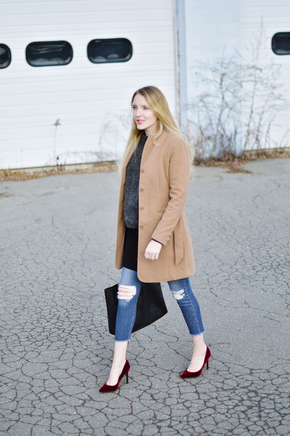 styling a layered winter outfit with this camel coat, chunky sweater, distressed denim, and velvet pumps