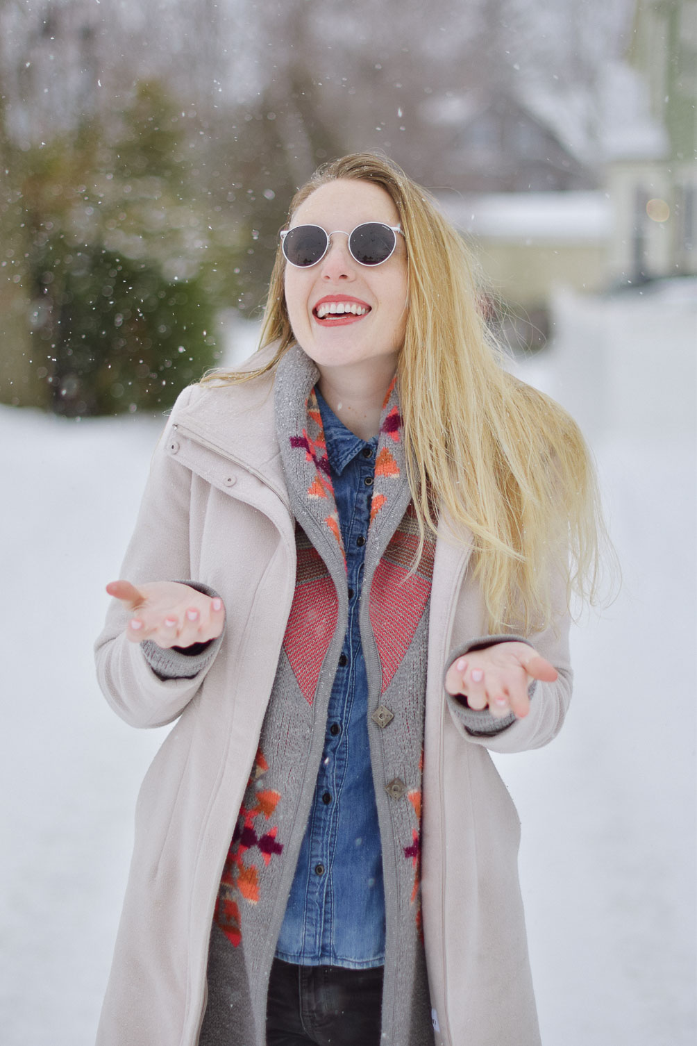 styling this cozy winter look with an aztec print sweater, chambray shirt, gray skinny jeans, and round sunglasses