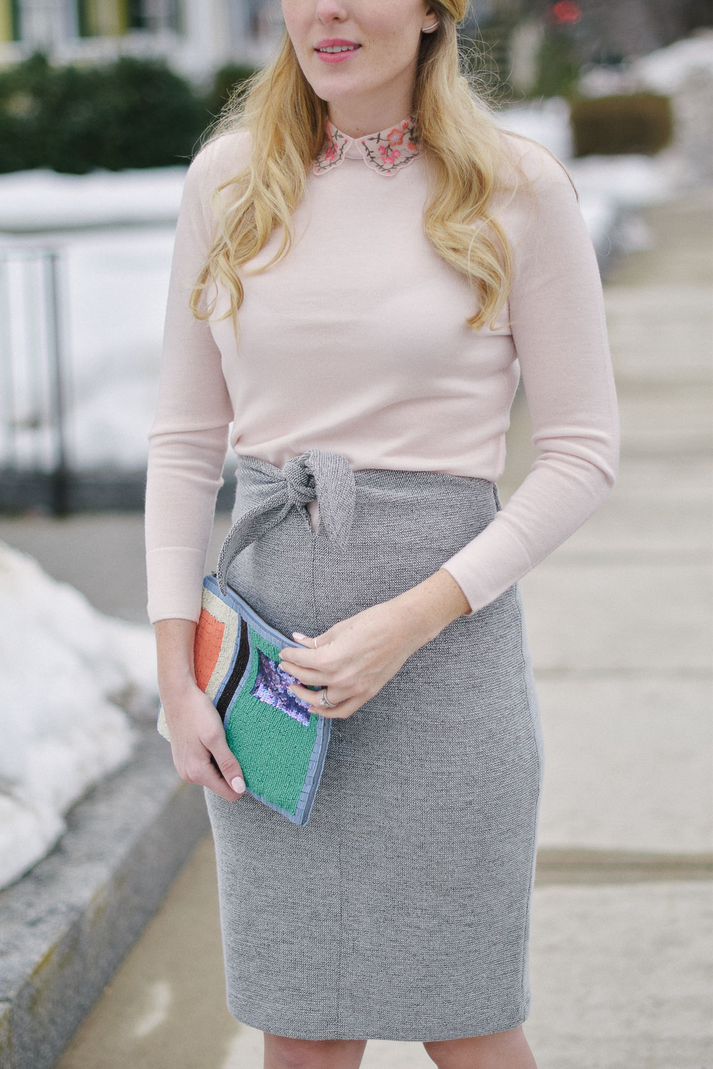styling an embroidered collar sweater with tie waist skirt and beaded clutch