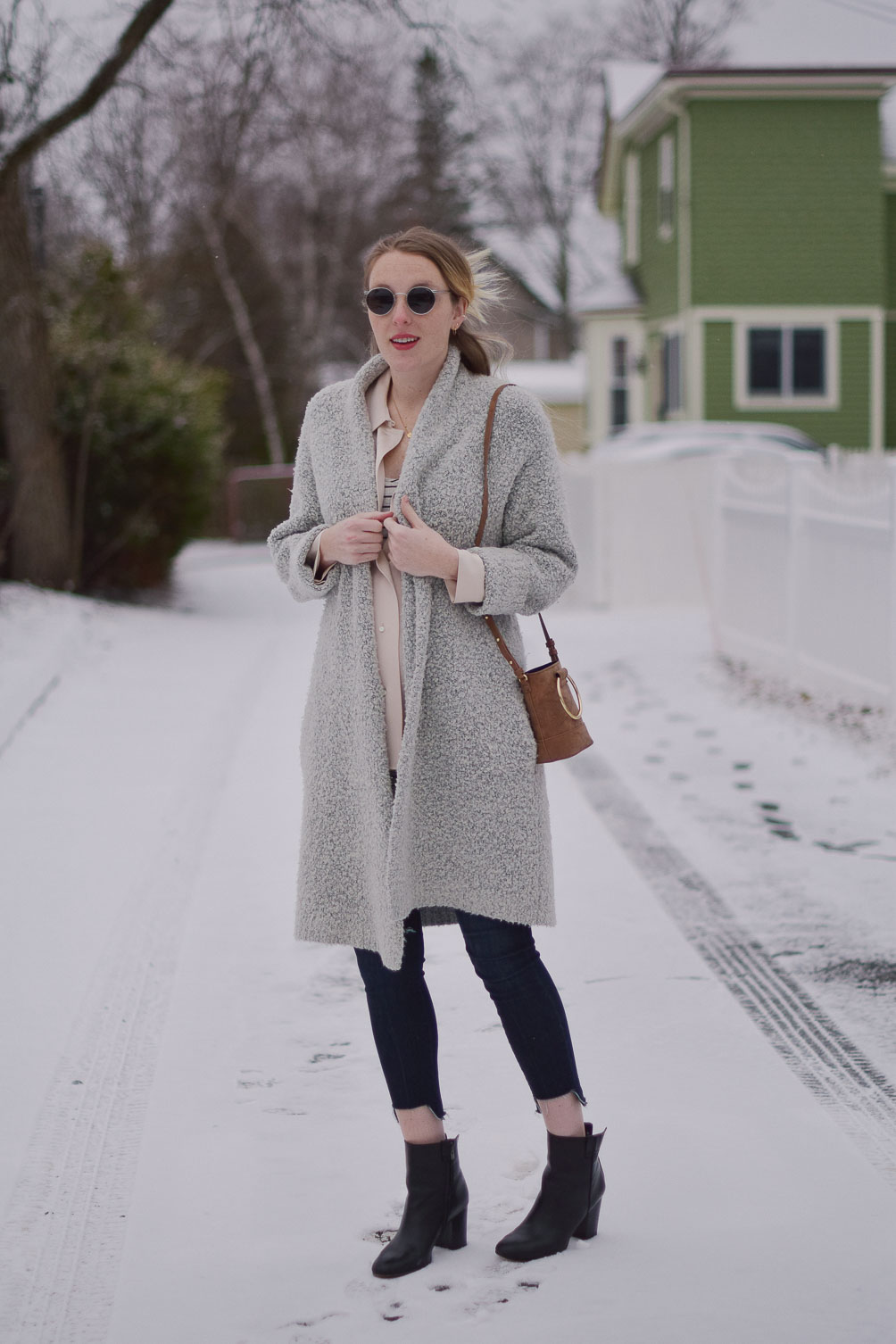 styling a faux suede mini bag with raw edge maternity jeans and an oversized cardigan