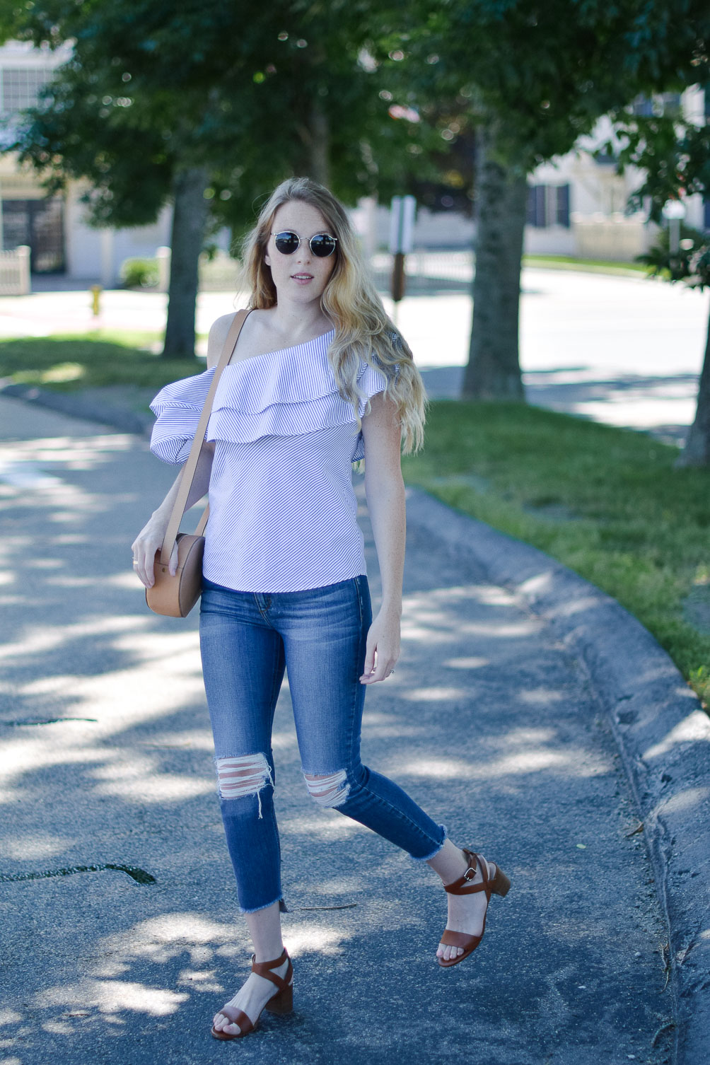styling a summer outfit with this one shoulder ruffle top and distressed skinny jeans