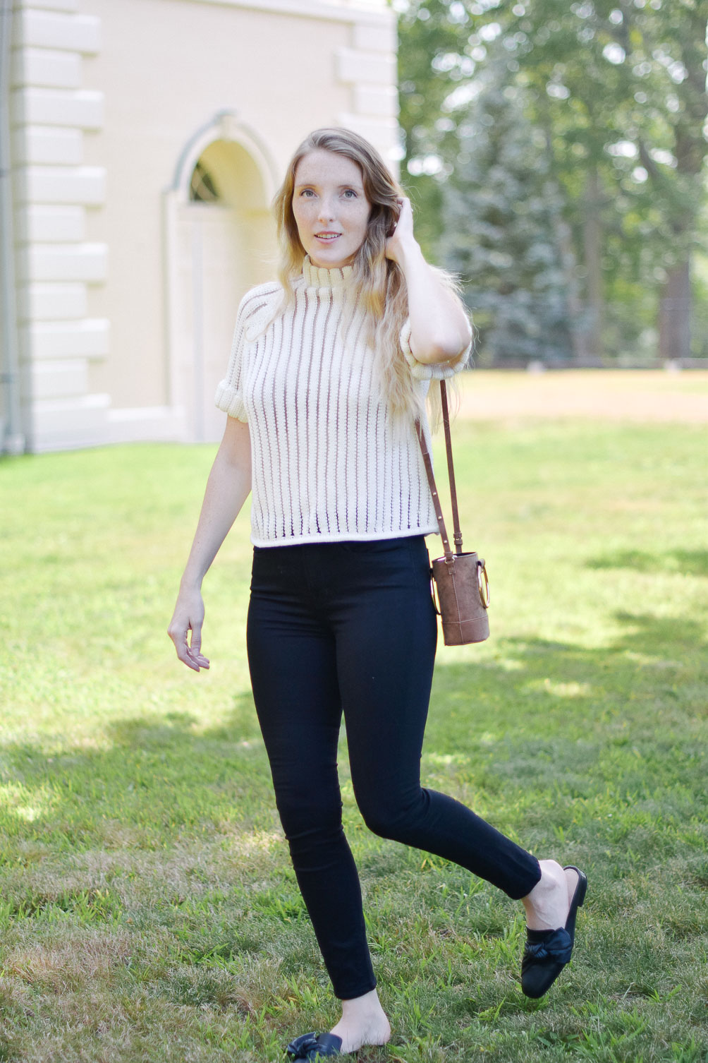 Leslie Musser styling a short sleeve sweater with black skinny jeans and leather mules for transitional fall style