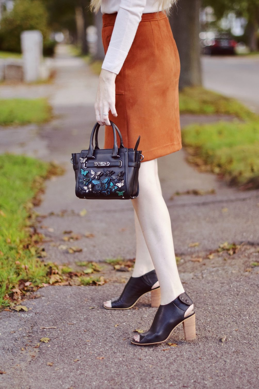 suede rust skirt on leslie musser with Club Monaco pink embroidered sweater and Coach appliqué bag for fall style outfit
