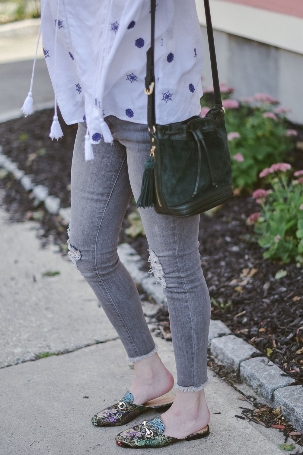 fashion blogger Leslie Musser styling the best bohemian tops for fall with gray denim, printed slides, and a suede bucket bag