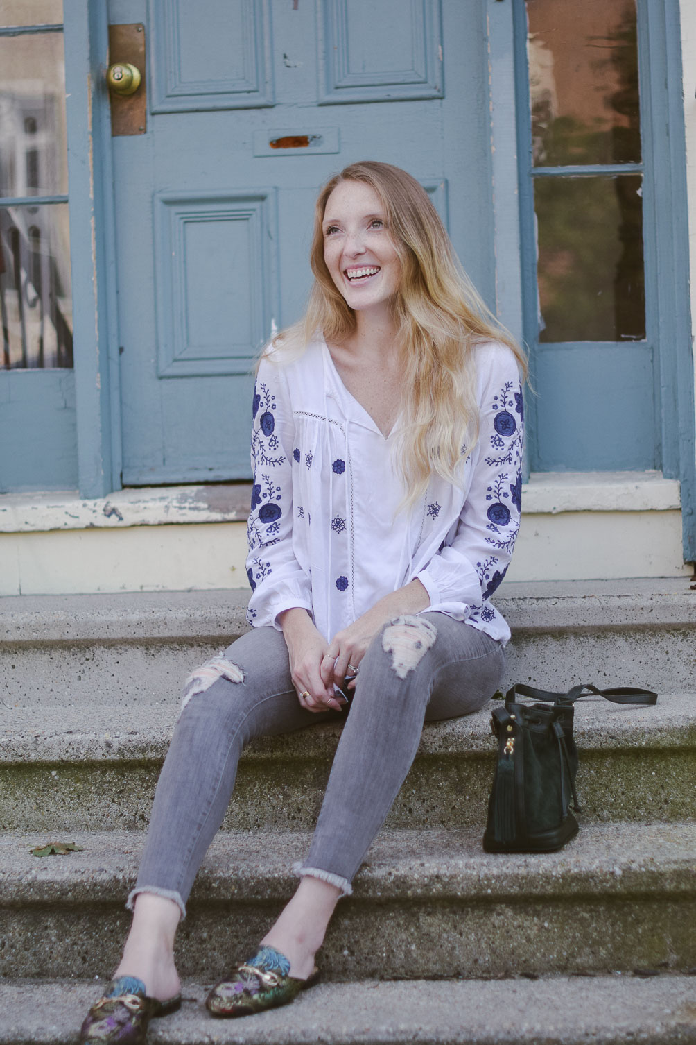 fashion blogger Leslie Musser styling the best bohemian tops for fall with gray denim, printed loafers, and a suede bucket bag