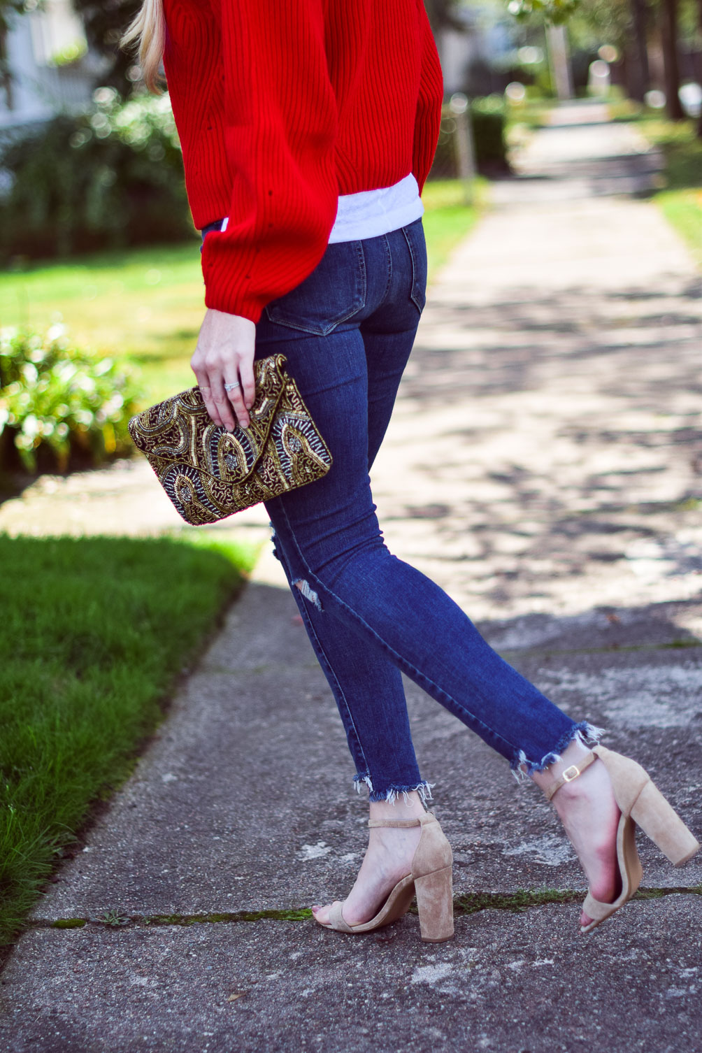 wearing a bright chunky red sweater with step hem jeans and block heel sandals