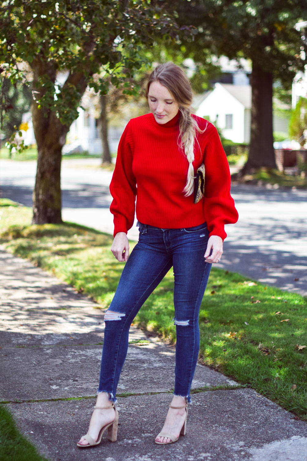 wearing a bright poppy red cashmere blend sweater with step hem jeans and block heel sandals