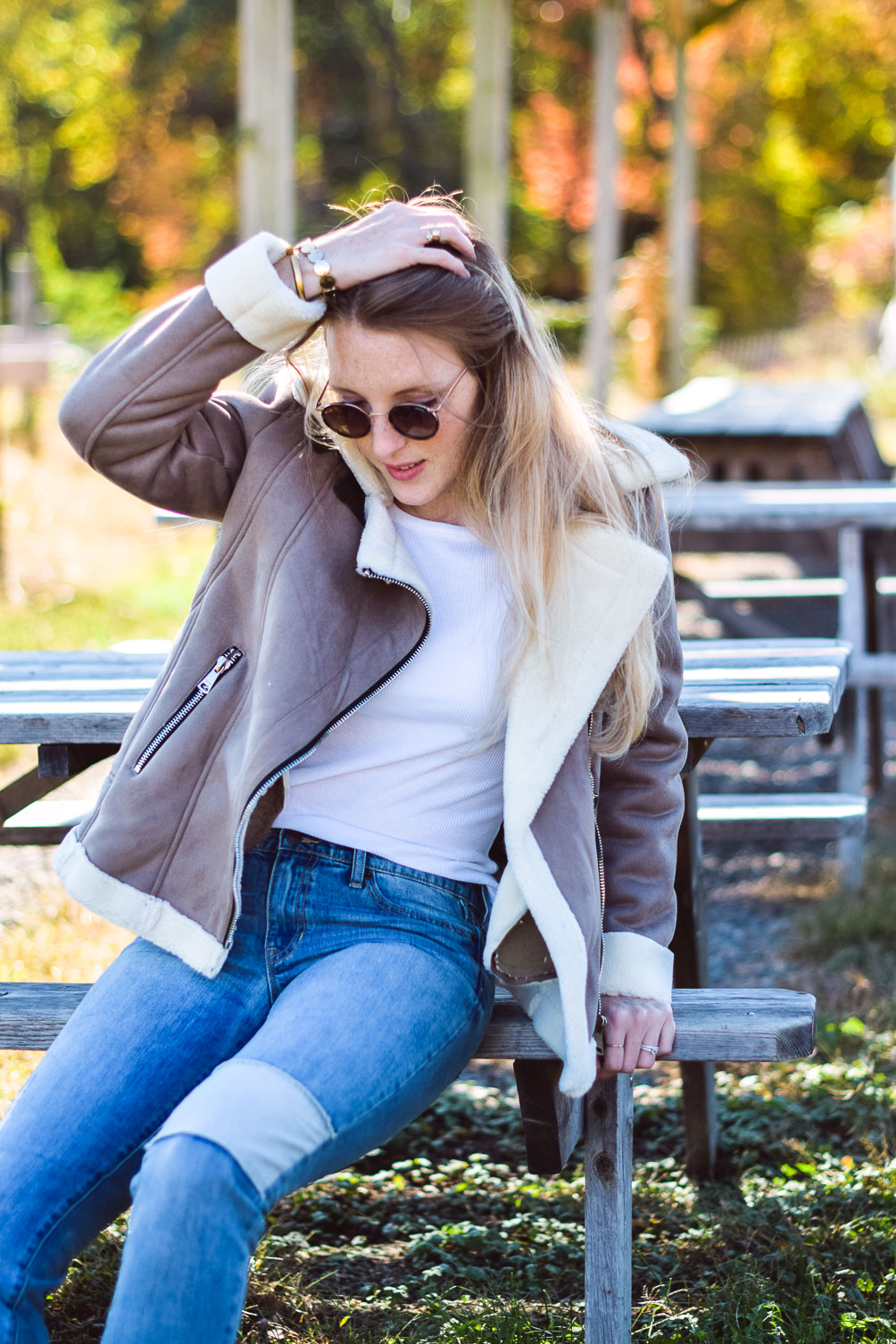 styling this faux suede moto jacket for fall and winter with a white henley, patched boyfriend jeans, and tan slides