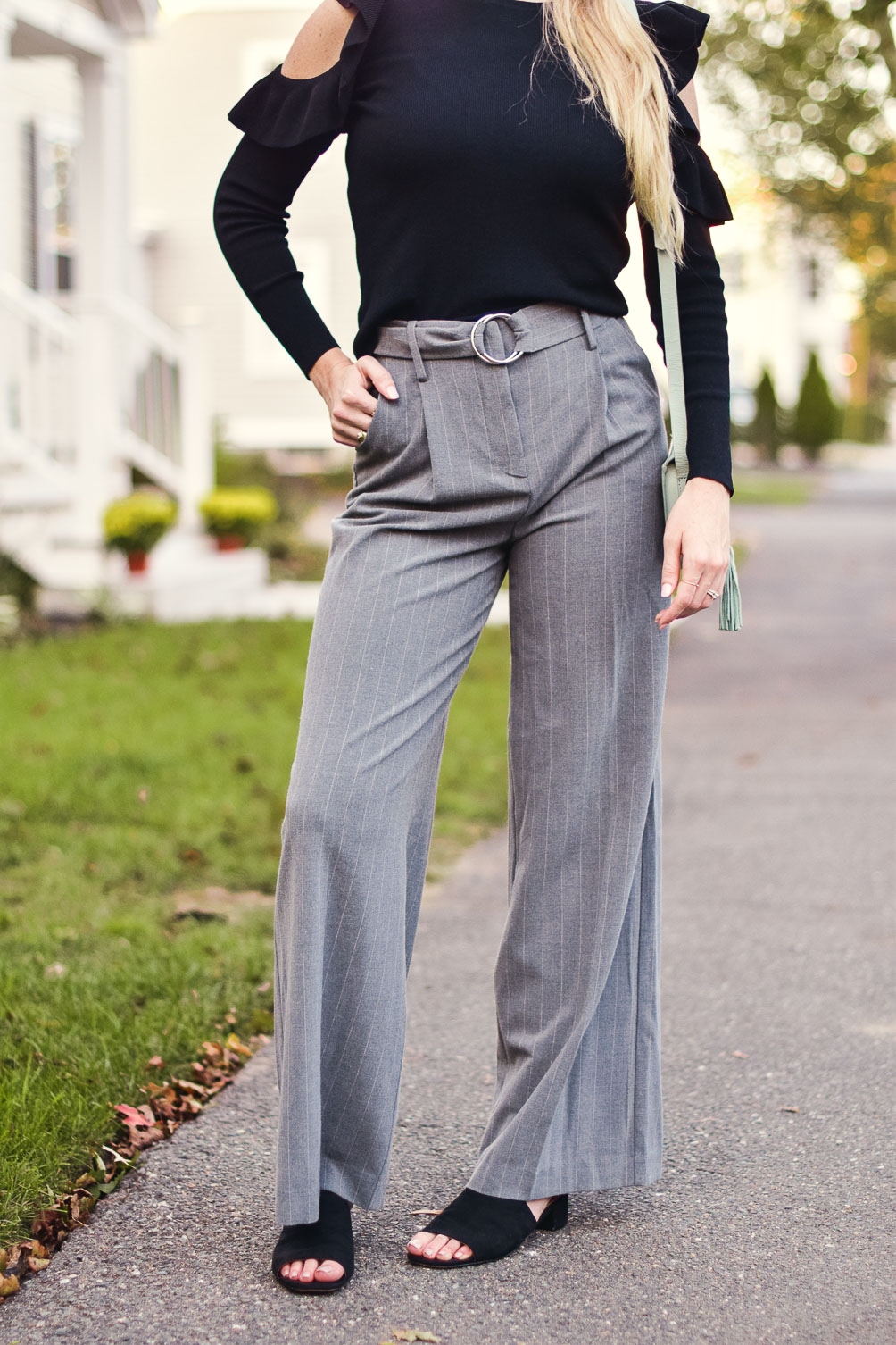 styling an easy classic holiday outfit for your work party with this cold shoulder ruffle sweater and pinstripe trousers
