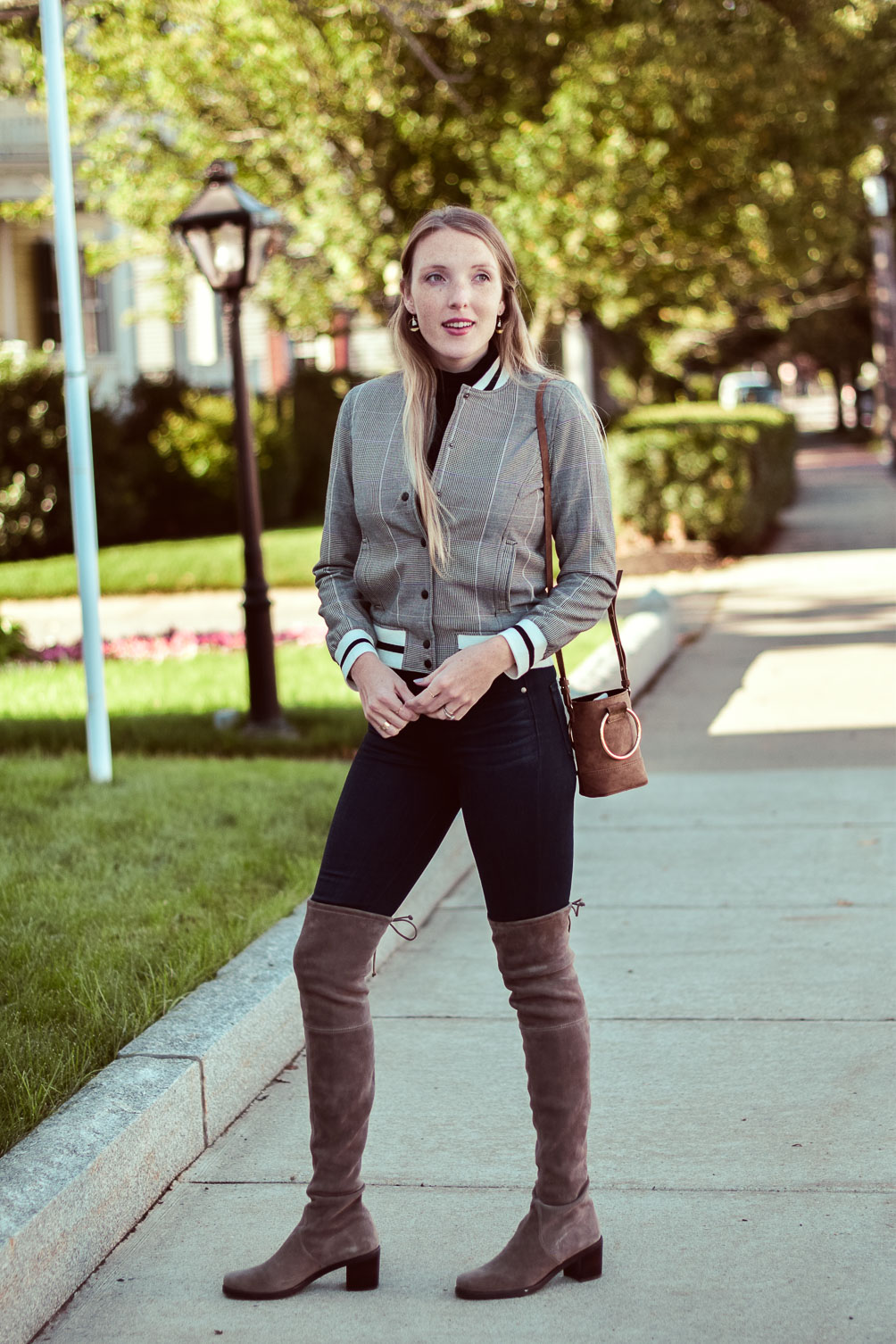 styling a Who What Wear varsity bomber jacket for fall with this black turtleneck, dark skinny jeans, and Stuart Weitzman over-the-knee boots
