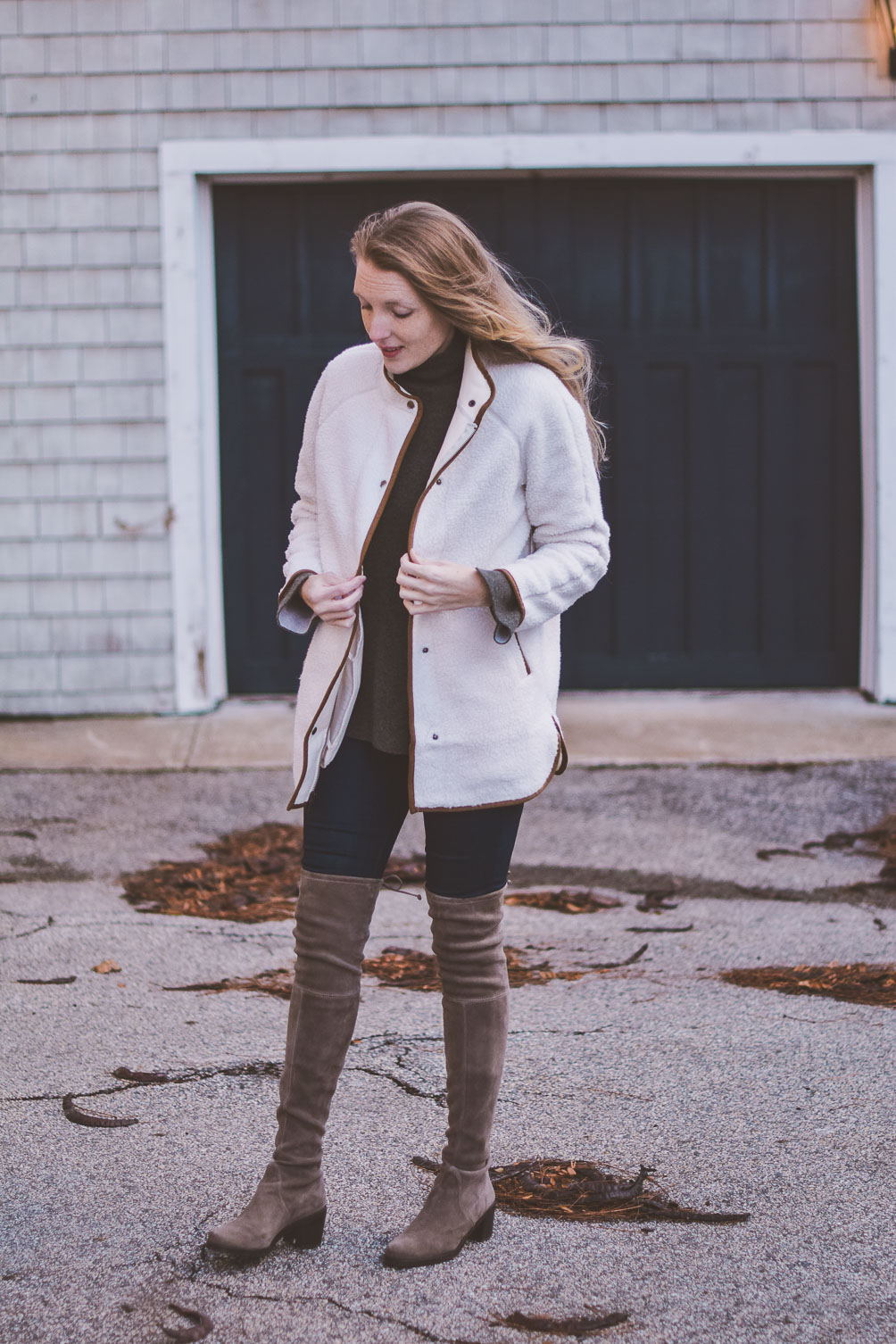 wearing a faux white sherpa jacket for styling neutrals with this cashmere sweater and over the knee Stuart Weitzman boots