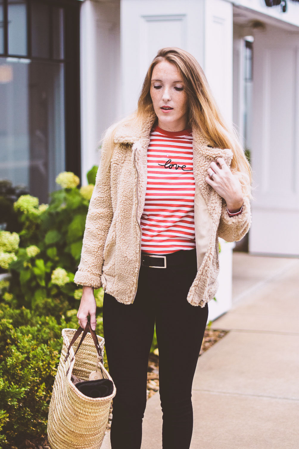 styling a teddy bear jacket as the best outerwear option for winter with a striped top and black skinny jeans