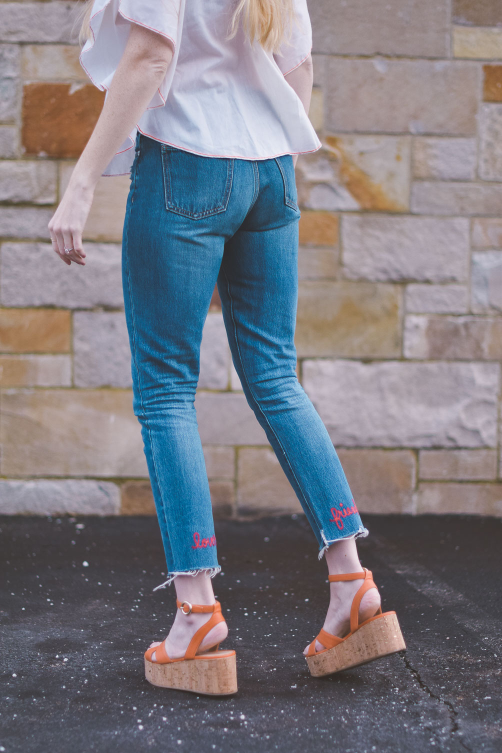 wearing an embroidered vintage top for spring with raw edge denim and cork platform sandals
