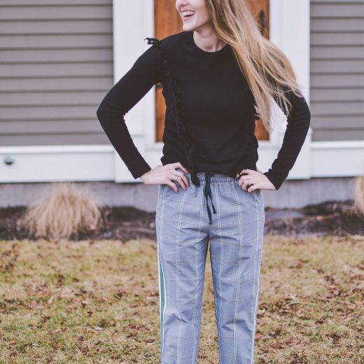 styling a modern checked track pant for everyday wear with black leather mules and a fringe sweater