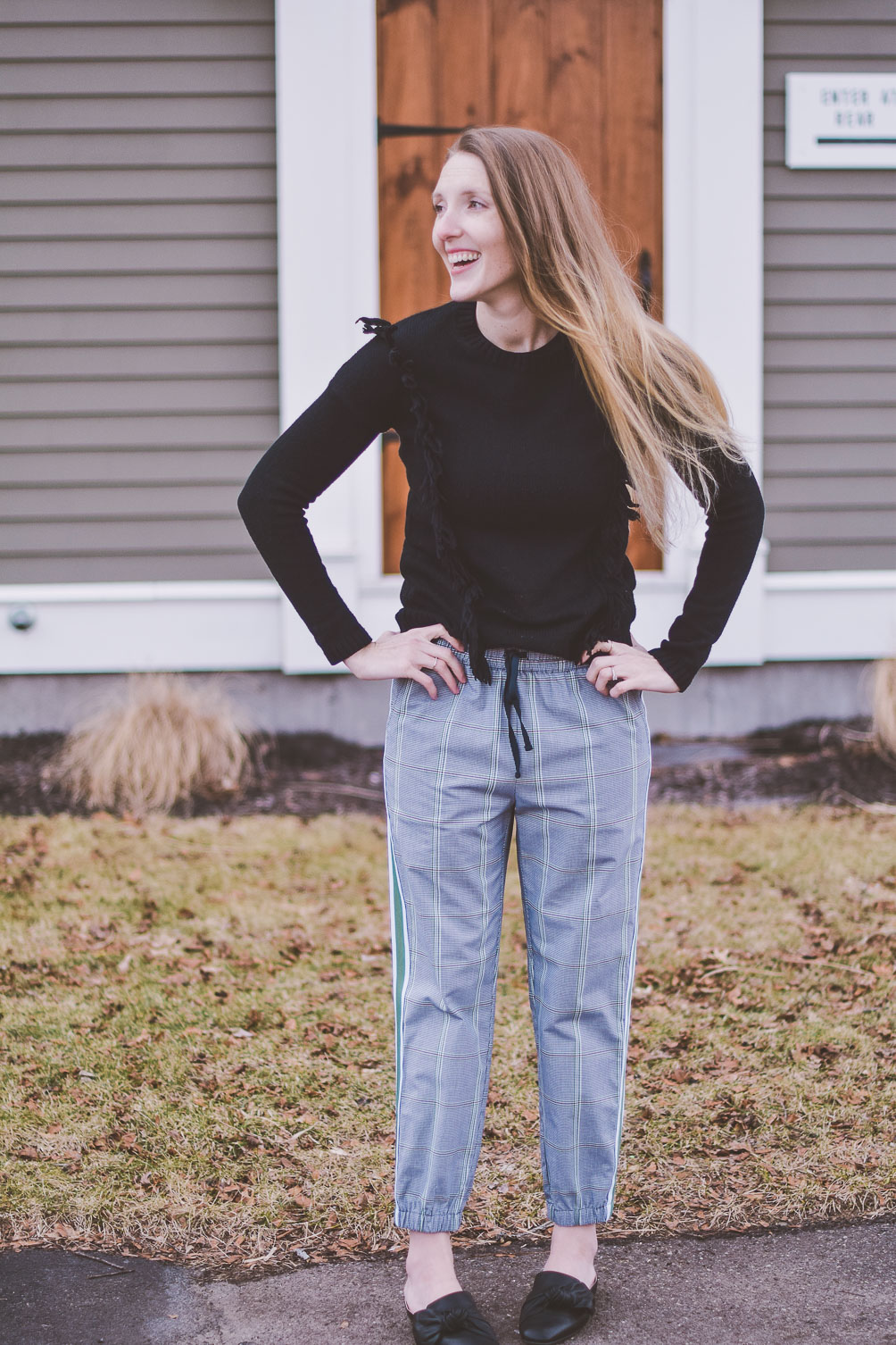 styling a modern checked track pants for everyday wear with black leather mules and a fringe sweater