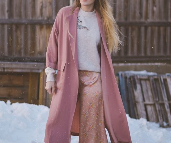 styling pastel pink for spring with a lightweight trench, appliqué sweater, silk trousers, and suede mules