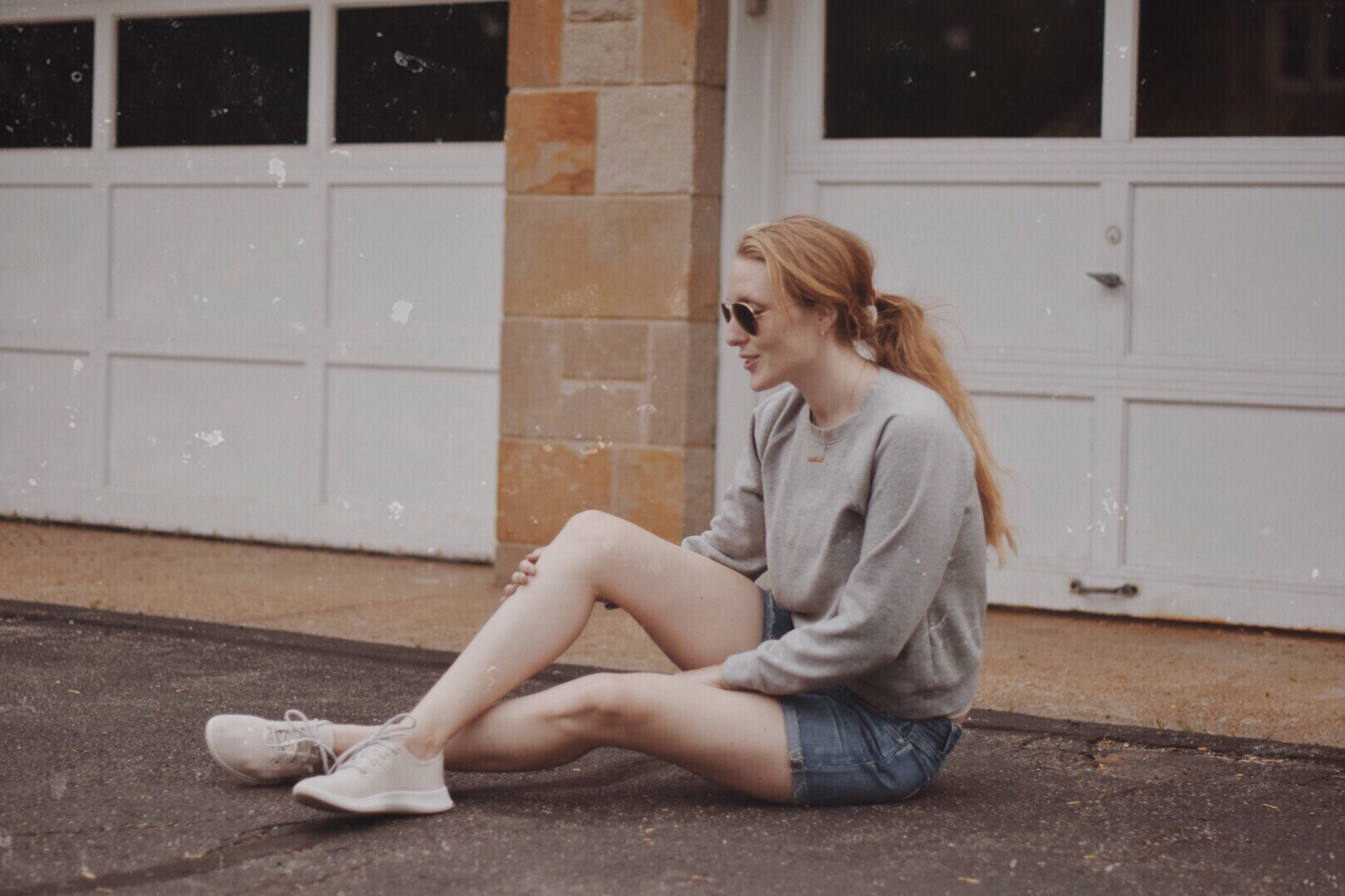 styling an easy casual summer outfit idea with sustainable fashion brands Everlane crewneck sweatshirt, Allbirds sneakers, cutoff shorts
